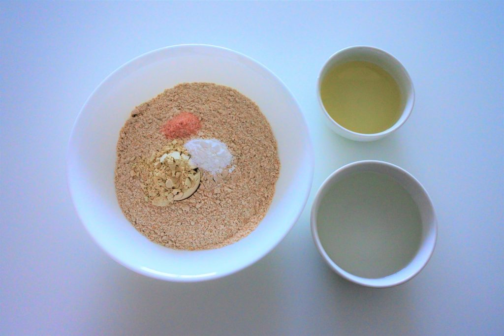 And overhead image of a bowl containing white whole wheat flour, vital wheat gluten, salt and baking power and two bowls to the right containing oil and water