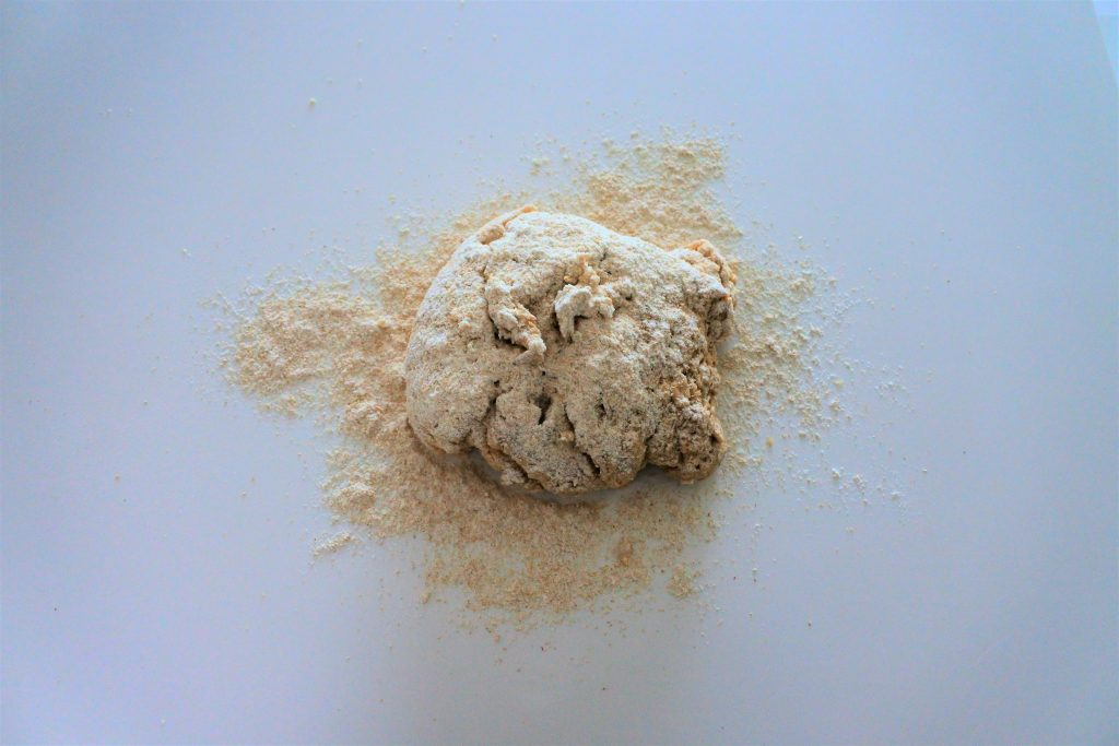 An overhead image of a mass of whole wheat dough covered in white whole wheat flour on a white counter top surface