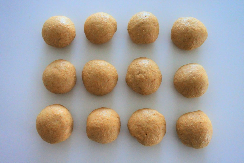 An overhead image of twelve balls of whole wheat tortilla dough on a white counter top.