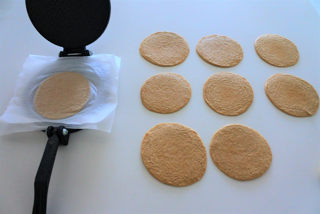 An angled image of rounds pressed tortilla dough on a white countertop with one dough round between two pieces of parchment paper that is sitting in an opened cast iron tortilla press