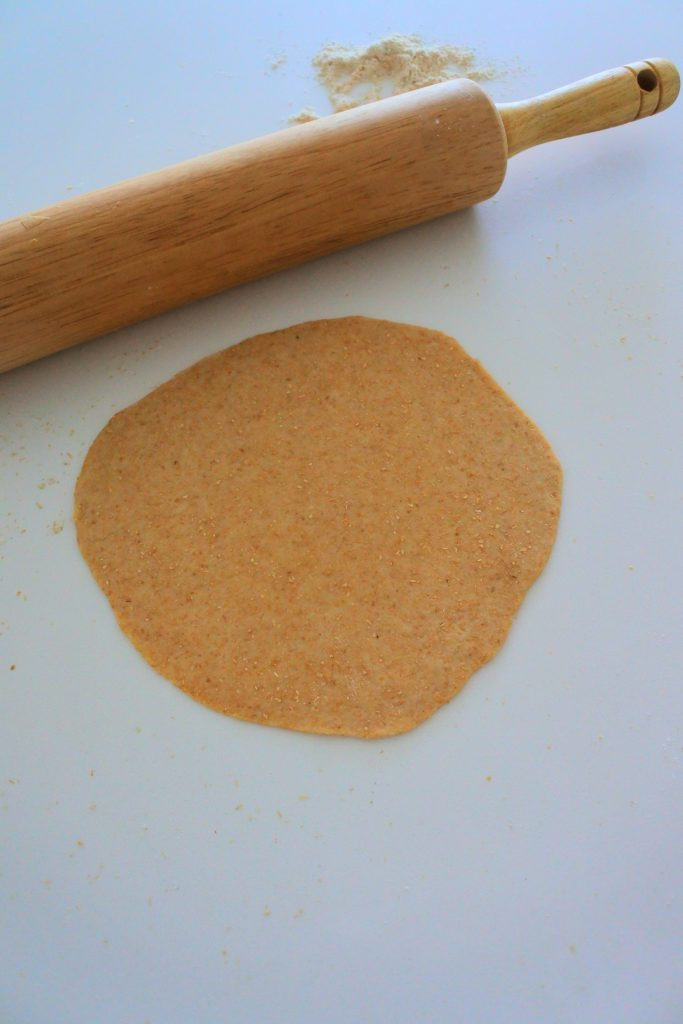 Overhead image of a round of tortilla dough rolled out against a white countertop with a rolling pin in the top left corner