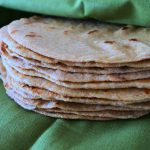 Close up image of a stack of whole wheat flour tortillas wrapped in a green linen napkin