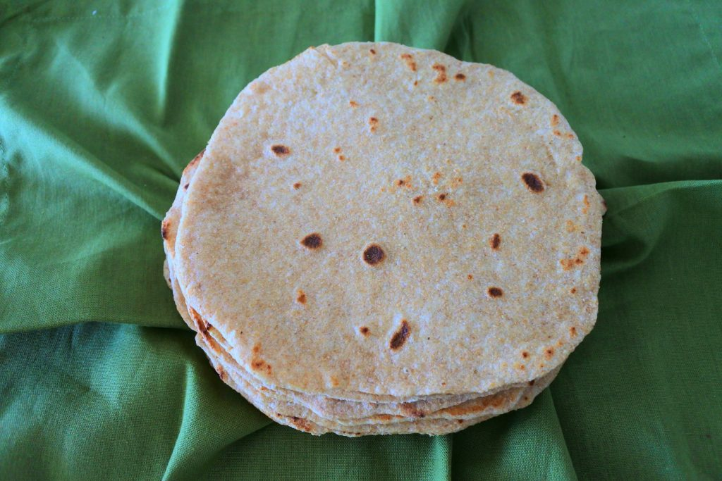 Overhead image of a stack of whole wheat flour tortillas sitting on top of a green linen napkin